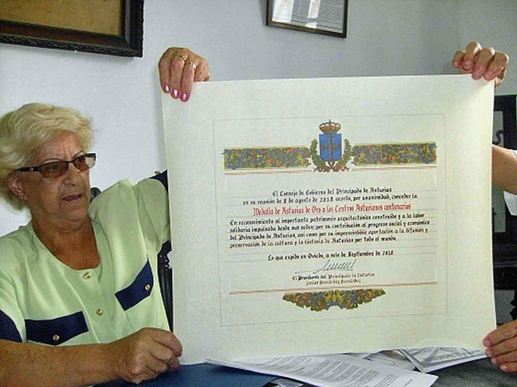 Ma Lidia Amago muestra el Diploma otorgado por el gobierno asturiano a 21 sociedades asturianas centenarias en Cuba.