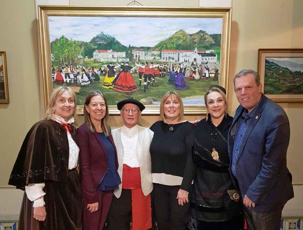 Julio Ríos, en el centro, junto a colaboradores posan bajo el cuadro 'Romería'.