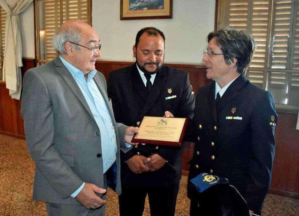 Román Nogueira entrega la placa de reconocimiento a la directora de la Banda, Natalia Sanabria.