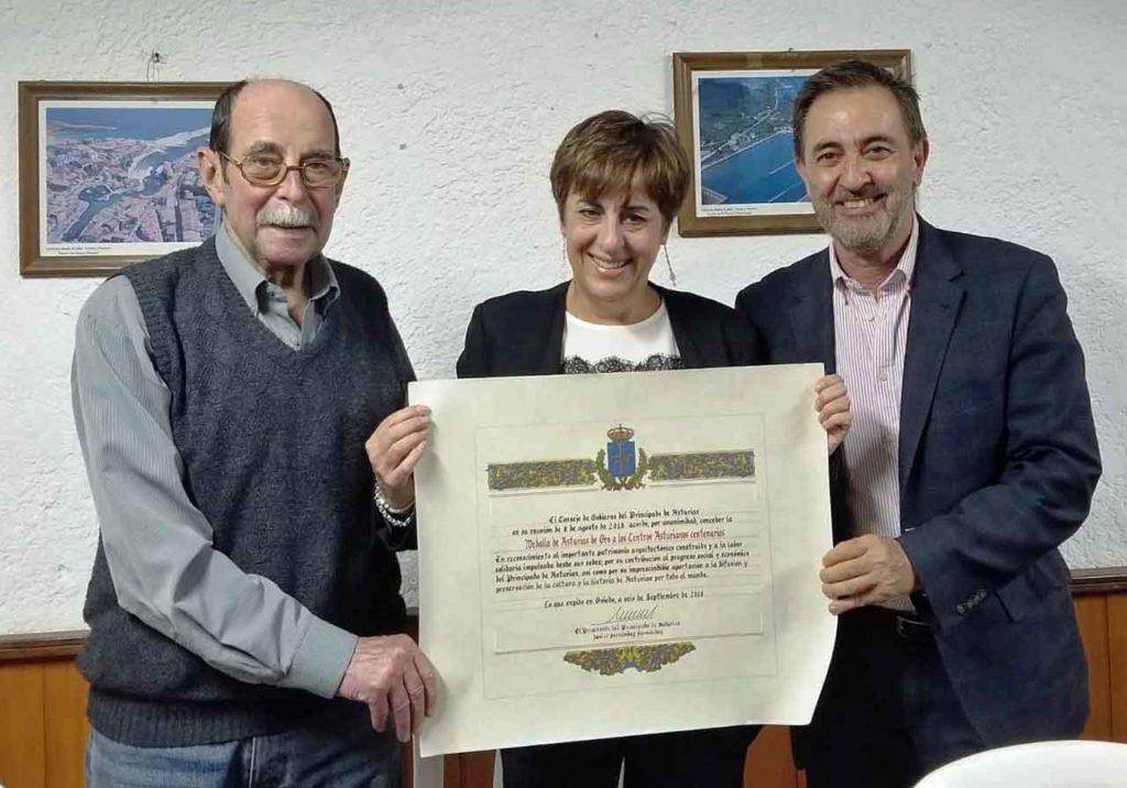 José Pérez, Begoña Serrano y José Rodríguez Moyano con el diploma entregado a la entidad con la Medalla de Asturias.