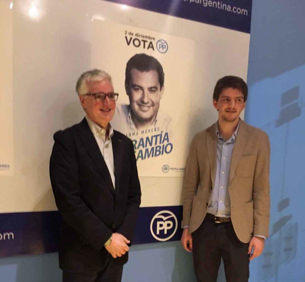 El presidente y el secretario general del PP en Argentina junto a la imagen del candidato, Juan Manuel Moreno Bonilla.