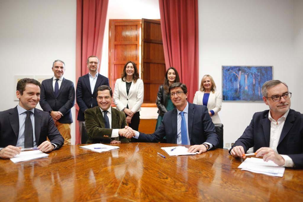Juan Manuel Moreno (izq.) estrecha la mano de Juan Marín, líder de C's en Andalucía.