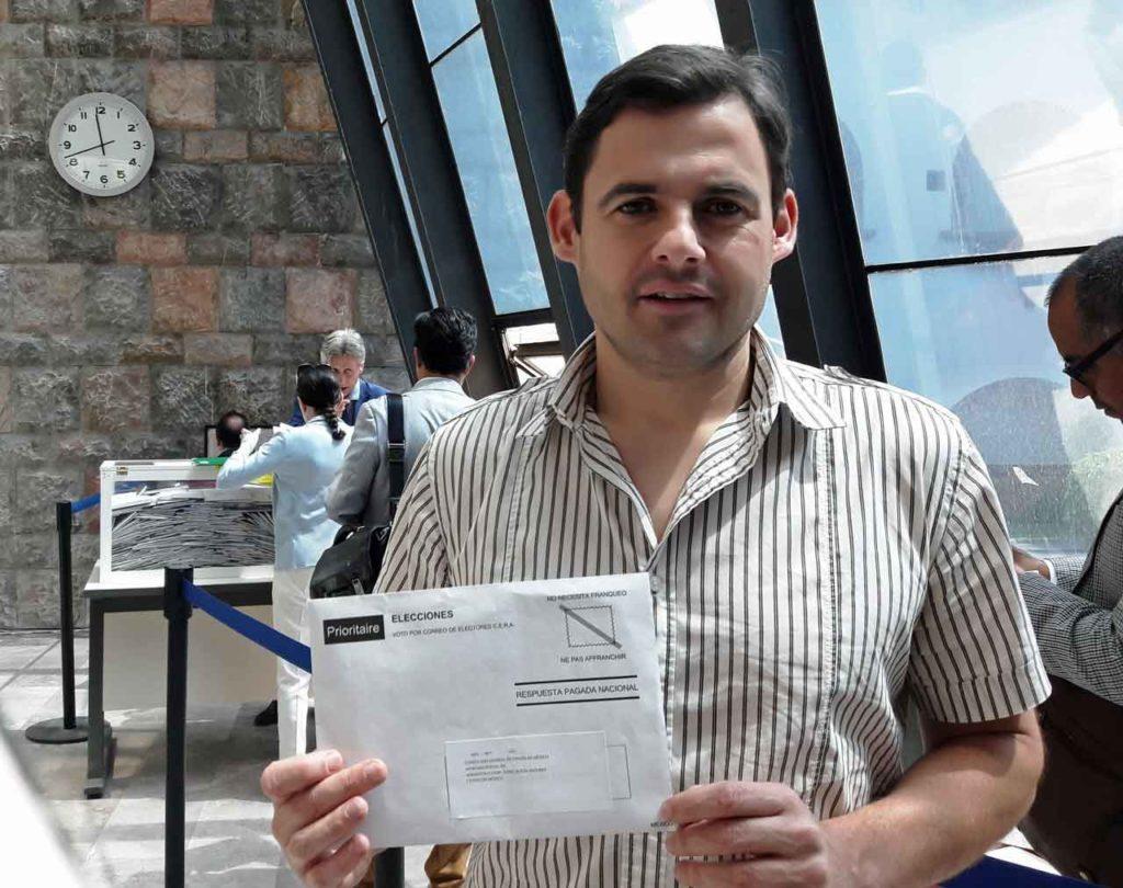 Un votante mostrando el sobre de votación justo antes de depositarlo en la urna.