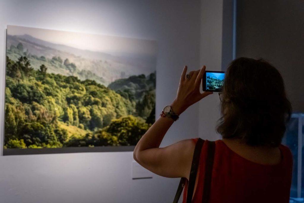 Una visitante fotografía una imagen de la muestra.