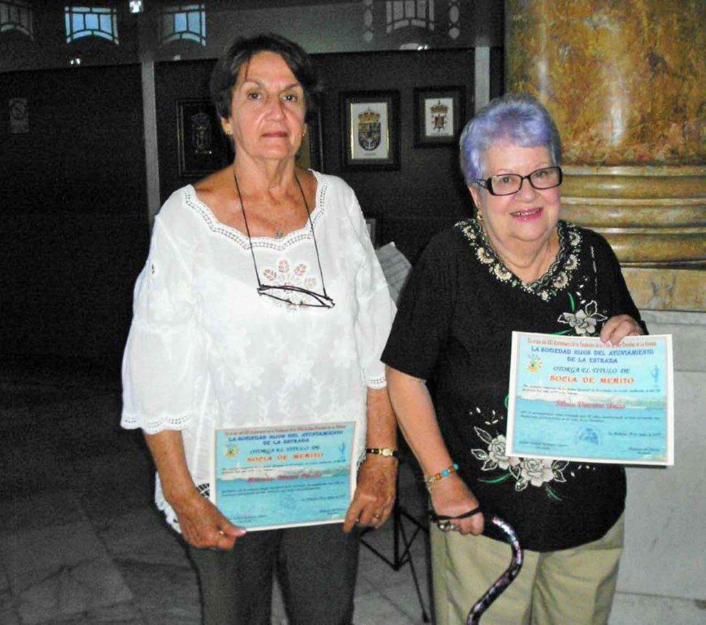 La primera mujer secretaria de la sociedad Mª Mercedes Blanco y la asociada cincuentenaria Silvia Vinceiro, (izq) recibieron el título de Socio de Mérito.