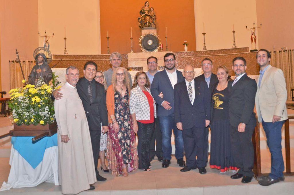 Asistentes a la misa posan junto a la imagen del Apóstol Santiago.