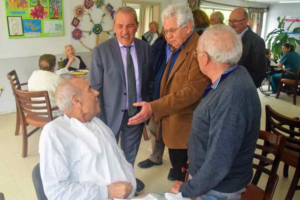 El secretario general de Inmigración y Emigración junto al presidente del Hogar, Ángel Domínguez, charlando con un residente.