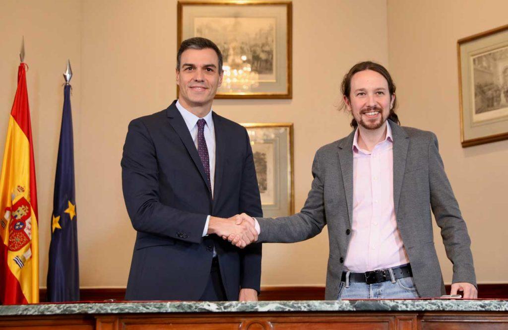 Pedro Sánchez (PSOE) y Pablo Iglesias (Unidas Podemos) se estrechan las manos en el acto de firma del acuerdo.