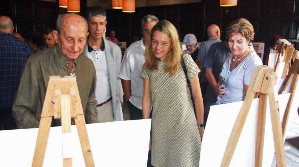 La ministra consejera Nuria Reigosa y sus acompañantes recorriendo la muestra fotográfica.