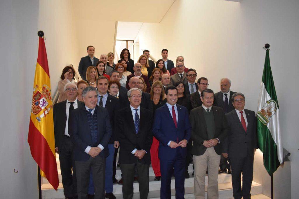 Moreno Bonilla y el resto de autoridades posan con los vocales del Consejo de Comunidades Andaluzas.