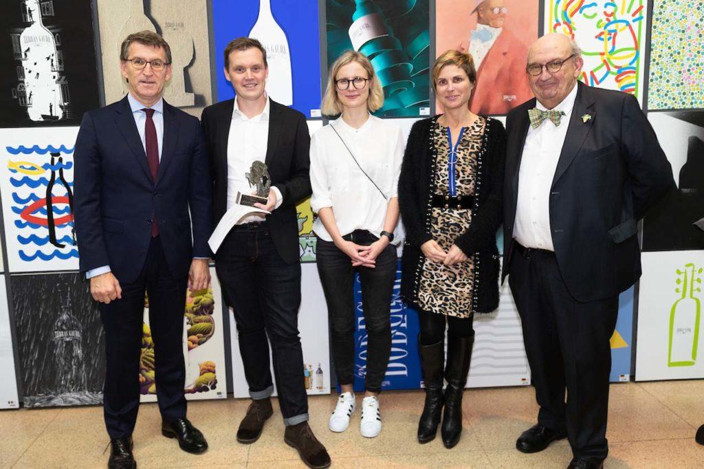 Feijóo, Fonseca Moretón y Nava Castro (4ª por izq.), directora de Turismo de Galicia, con los ganadores del Concurso ante las obras finalistas.
