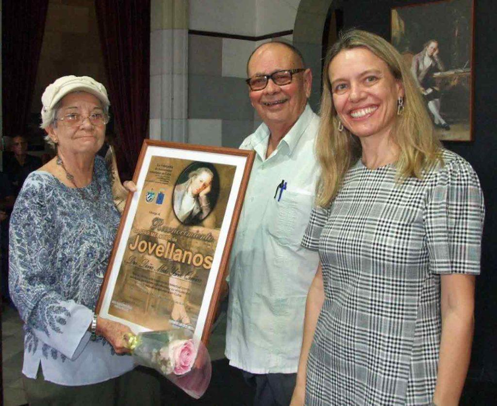 Mirta Yáñez recibió el Reconocimiento Jovellanos de manos de la ministra consejera Nuria Reigosa y del presidente de la FAAC, Longinos Valdés.
