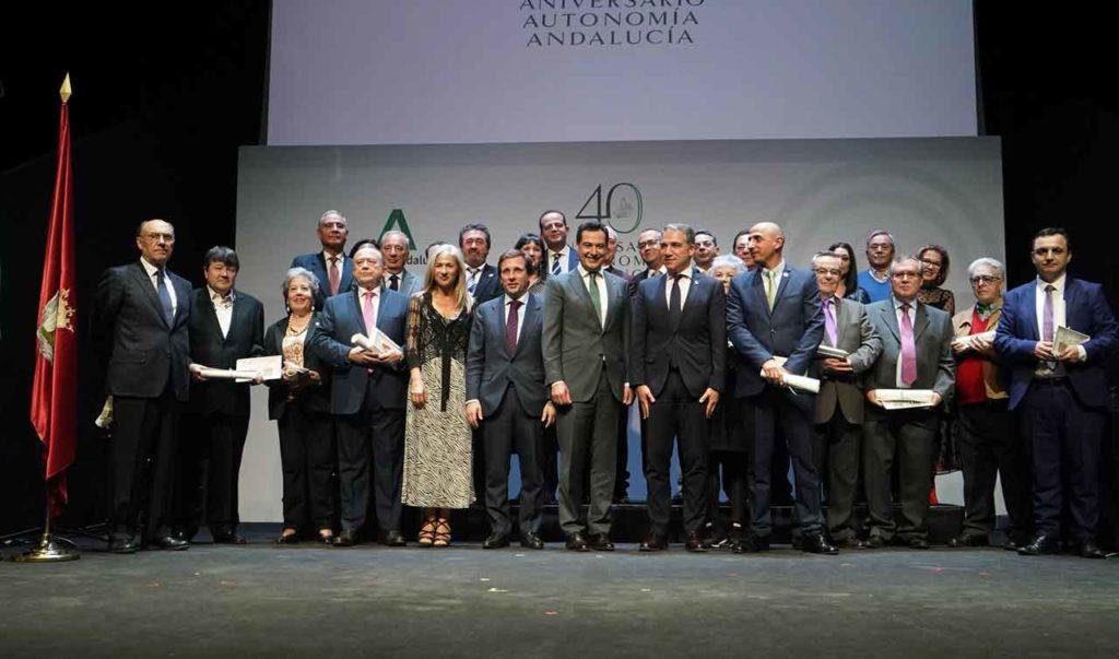 Juan Manuel Moreno posa en el escenario con los participantes en la celebración del 28-F en Madrid.