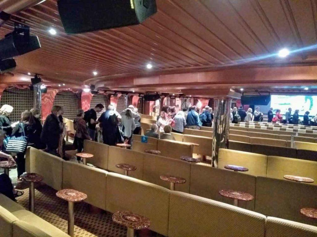 Los pasajeros forman cola para descender del buque.