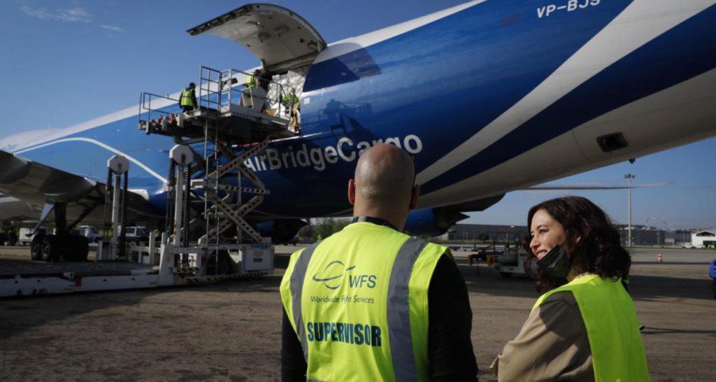 Isabel Díaz Ayuso, junto al avión, durante la descarga del material.