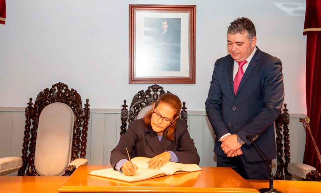 Ela Méndez firmando en el Libro de Honor del Ayuntamiento de Ortigueira junto al alcalde Juan Penabad.