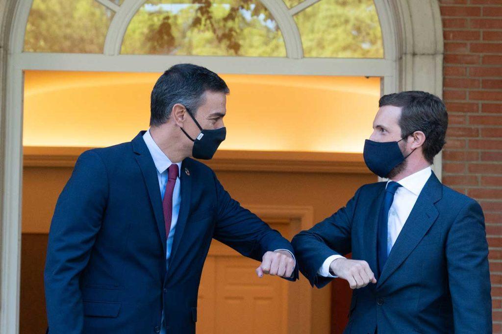 Pedro Sánchez y Pablo Casado se saludan con el codo antes de su reunión en Moncloa.