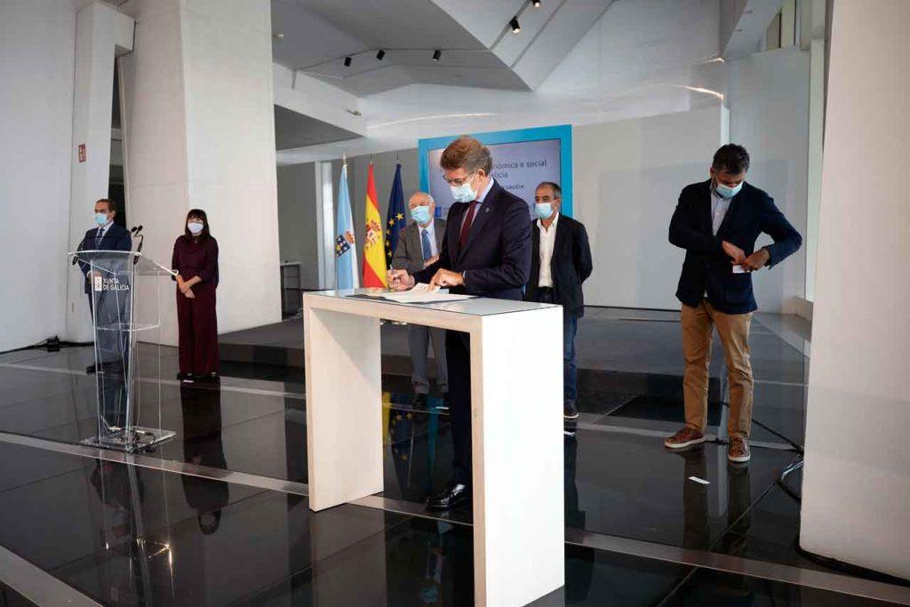 El titular del Gobierno gallego, Alberto Núñez Feijóo, firma la declaración institucional acompañado por otros miembros del Ejecutivo autonómico y de la Mesa del Diálogo Social.