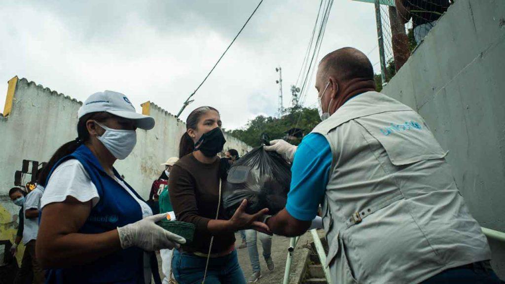 Personal de Unicef entrega a una mujer un kit de alimentos en las afueras de Caracas. © Unicef Venezuela
