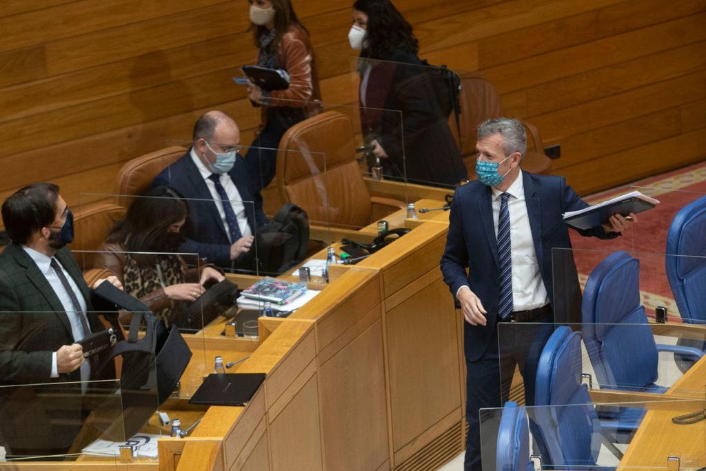 El diputado del PP, Alberto Pazos (izquierda), dialoga con el vicepresidente primero de la Xunta, Alfonso Rueda, tras su intervención.