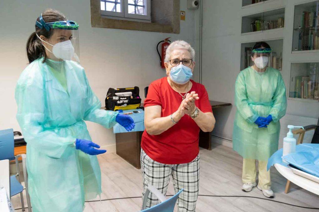 Nieves Cabo Vidal, usuaria de la residencia de mayores Porta do Camiño de Santiago de Compostela, aplaude tras ser la primera persona vacunada en Galicia frente a la Covid-19.