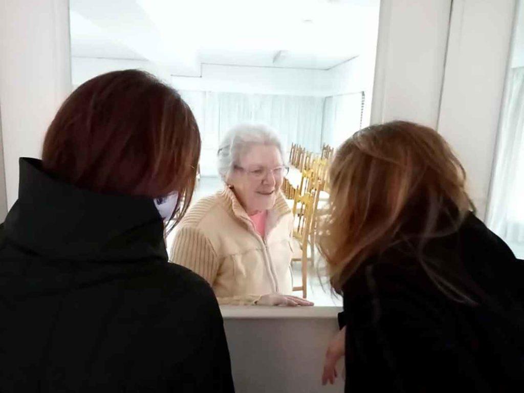 Una residente del Hogar charlando con sus familiares a través de una puerta de vidrio antes de que se suspendieran las visitas.
