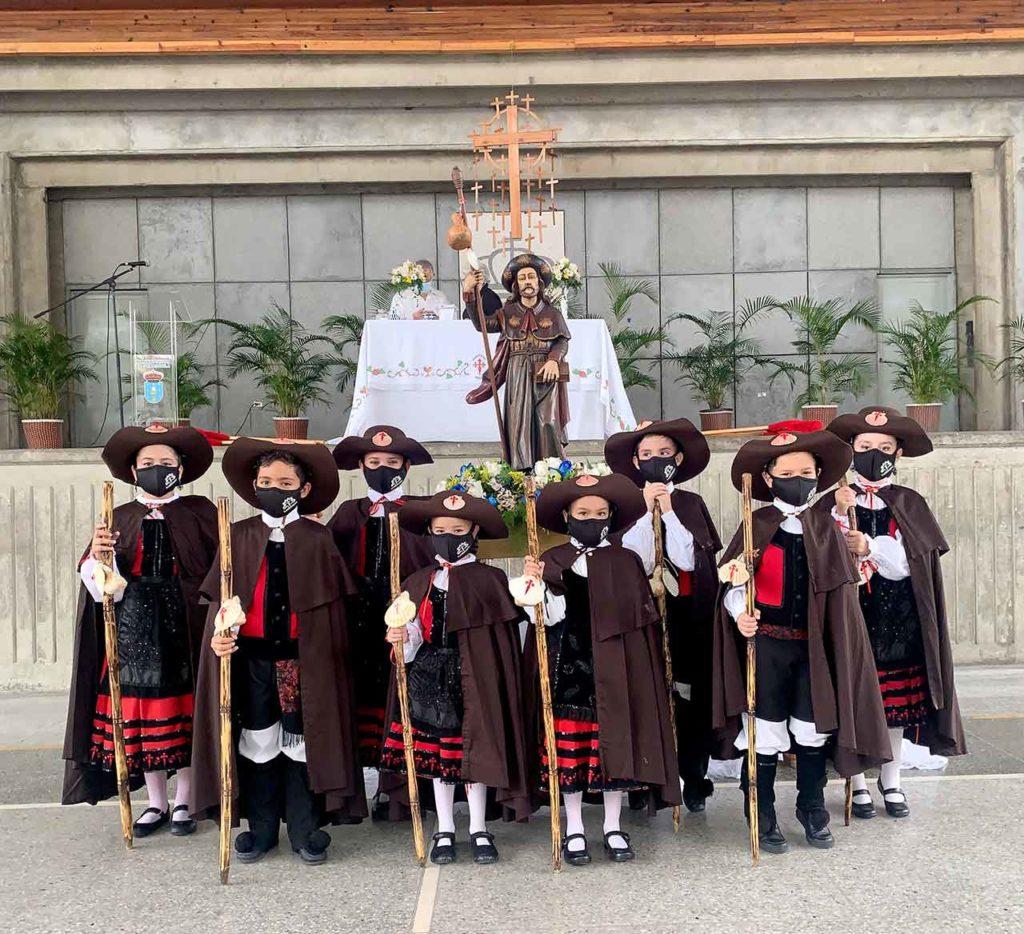 Los más jóvenes de la Hermandad Gallega de Venezuela ataviados como peregrinos ante la imagen del Apóstol Santiago.