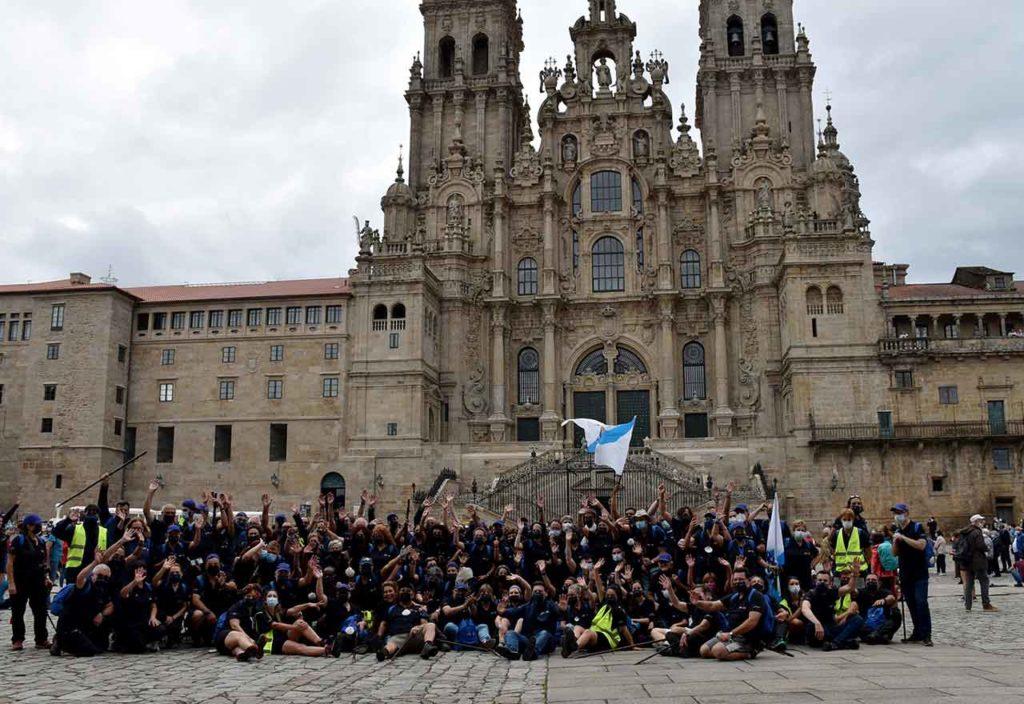 Foto de familia de los participantes en 'Conecta co Xacobeo' con el secretario xeral da Emigración en la Plaza del Obradoiro.