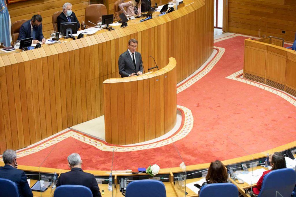 El presidente de la Xunta de Galicia, Alberto Núñez Feijóo, durante su intervención en el Debate sobre el estado de la Autonomía en el Parlamento gallego con el escaño que ocupaba Valeriano Martínez en primer término decorado con una flor y con sendos ejemplares de la Constitución española y del Estatuto de Autonomía de Galicia.