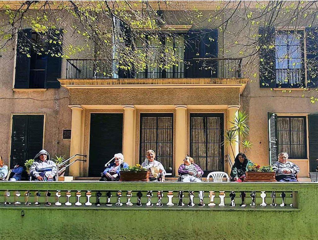 Algunos residentes disfrutando del buen tiempo en la terraza del Hogar.